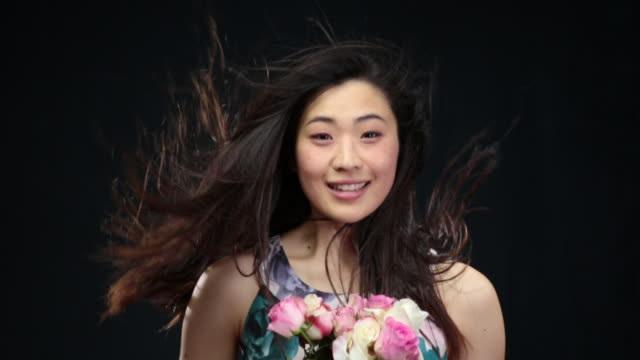 MS SLO MO Asian woman throwing head back, looking up,laughing,hair moving in wind / London, Greater London, United Kingdom