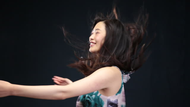 MS Asian woman turning around in circles,hair moving in wind / London, Greater London, United Kingdom
