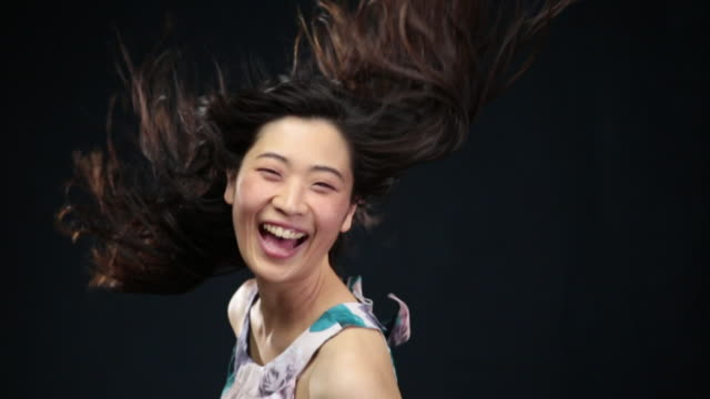 MS SLO MO Asian woman turning toward ,laughing, hair moving in wind / London, Greater London, United Kingdom