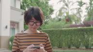 Asiatische Frau nutzt Smartphone im Garten bei Sonnenuntergang