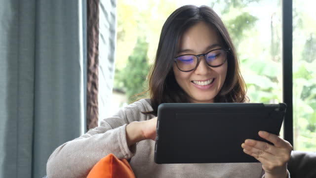 Asian Woman Using and Looking on Tablet With Glasses