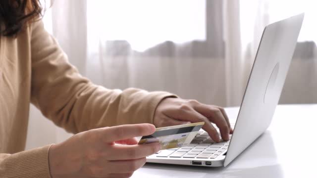 Asiatisk kvinna med kreditkort för online shopping hemma, nära upp