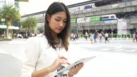 Asian woman using digital tablet in city