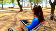 Asian woman using digital tablet in park