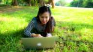 Asian woman using Laptop in the park