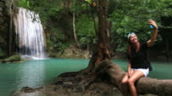 Asian woman using smartphone take a photo waterfall in Nature