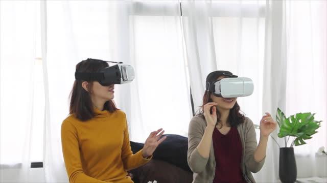 2 asiatische Frau mittels Virtual Reality im Schlafzimmer