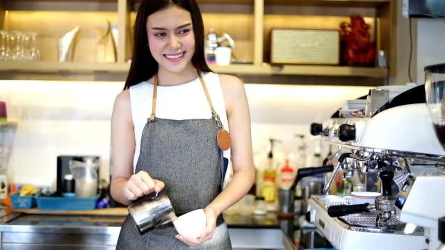 Asiatische Frauen Barista lächelnd und halten Kaffeetasse und Kaffee-Automaten shop counter - Frau Kleinunternehmen Besitzer Essen und trinken Café Arbeitskonzept