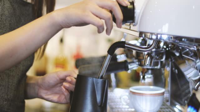 Aziatische vrouwen Barista lachend en met behulp van koffiemachine in koffie shop teller - werkende vrouw klein bedrijf eigenaar voedsel en drinken café concept