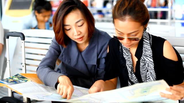 HD:2 Asian women looking the map.
