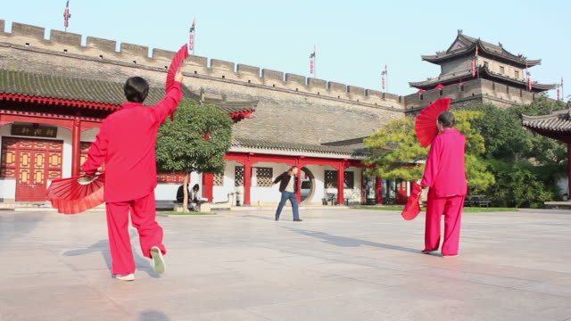 WS LA Asian women performing exercise with fans in city wall Park/xian,shaanxi,China