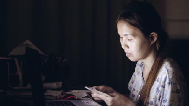 Asiatische Frauen sitzen im Wohnzimmer mit Laptop zu Hause in dem Schlafengehen