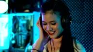 DJ asian women tweak various track controls on dj's deck
