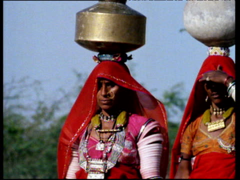 Asian women wearing traditional dress carry pots on head