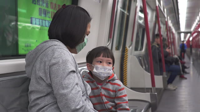 Asian women with her son wear mask to protect germ during transportation by train.