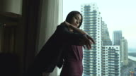 Asian young businesswoman putting on her suit.