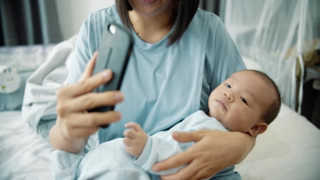 Asian young mother and baby boy sitting on bed while making video call on smart phone