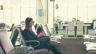 Asiatische junge Mutter und Tochter auf Smartphone am Tor warten im Flughafen Terminal