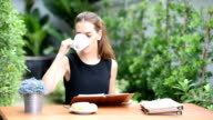 asian young woman drink a cup of coffee on table in the garden