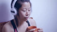 Asian young woman listening music and taking coffee break.