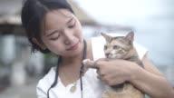 Asiatische junge Frau mit Katze spielen.