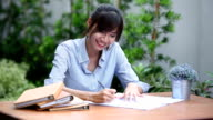 asian young woman sitting on workplace and writing on paper in the garden