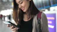 Asian young woman using Smart phone with passport at Airport, Traveling