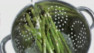 Asparagus being washed in super slow motion
