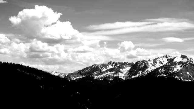 Aspen, Colorado, schwarz und weiß Zeitraffer Wolken Gebäude über Aspen Highlands schneebedeckten Gipfeln gekrönt und der tiefe Elk Mountain Valley