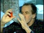 Asthma sufferer using inhaler R23030201 Drug packages on display in chemist shop