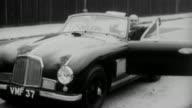 1952 B/W Aston Martin driving on highway / United Kingdom