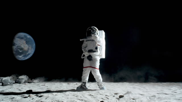WS SLO MO Astronaut doing the moonwalk and dancing on the moon / Berlin, Germany