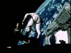 Astronaut Edward White floating in space above Earth during Gemini IV mission spacewalk