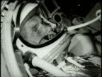 Astronaut John Glenn wears a spacesuit as he rides in a space capsule