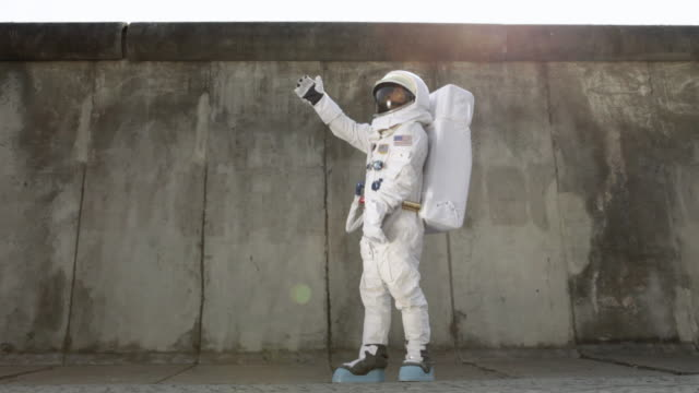 WS Astronaut on city sidewalk holding balloon and then releasing it / Berlin, Germany