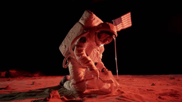 WS ZI SLO MO Astronaut on Mars collecting soil sample / Berlin, Germany