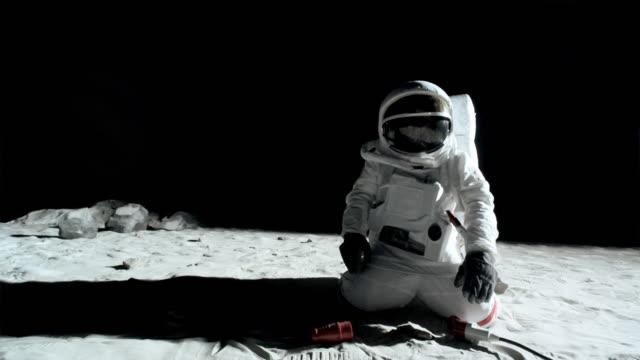 WS SLO MO Astronaut on the moon plugging in cord to extension cord and turning on the Earth / Berlin, Germany