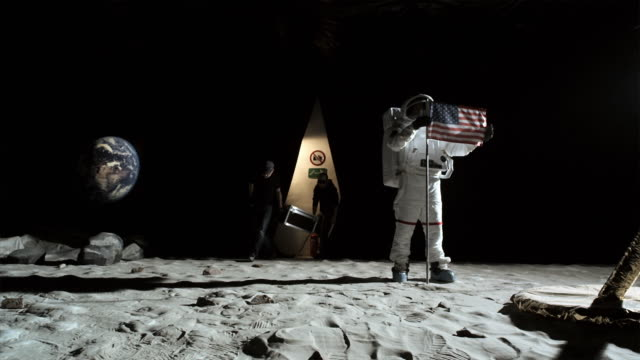 WS SLO MO Astronaut putting up American flag and two men carrying equipment coming through curtain onto the set / Berlin, Germany