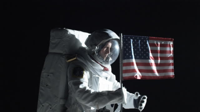 MS SLO MO Astronaut putting up American flag on the moon and saluting / Berlin, Germany