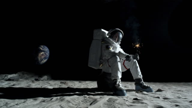 WS PAN SLO MO Astronaut sitting on rock on the moon lighting and then holding sparkler / Berlin, Germany