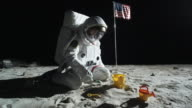 WS ZO SLO MO Astronaut sitting on the moon's surface playing with sand pail and shovel / Berlin, Germany