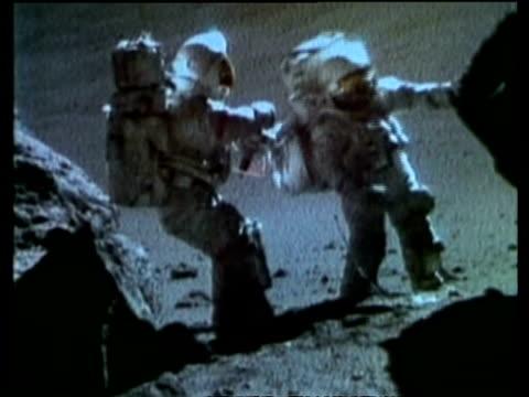 Astronauts, Schmitt and Cernan collecting samples between two boulders, Moon