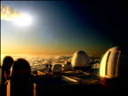 Astronomical observatories under bright sky huge meteorite with smoking tail shoots past in background