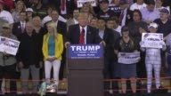 At a rally in Orlando US Republican presidential candidate Donald Trump asks protesters who are protesting to wait for five minutes