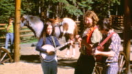 RV at camping site / Young girl writing in journal / Mother reading note / Playing Cards / Country band / Camping in Alberta Canada on May 01 1971 in...