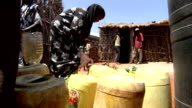at distribution point Woman refugee pouring water into bucket on July 30 2011 in Road from Nairobi to Garissa Kenya