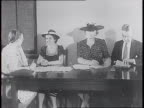 At headquarters of the American Committee for the Care of European Children workers on telephones at table / women lined up at a desk where a workers...