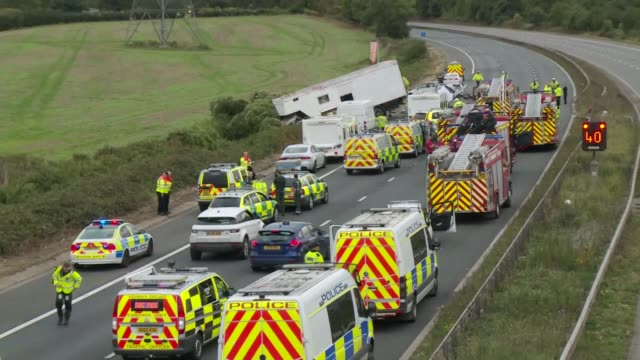 At least 4 people killed in crash on M5 ENGLAND Gloucestershire M5 EXT Wide shot of lorry in ditch at crash scene with fire engines and police...