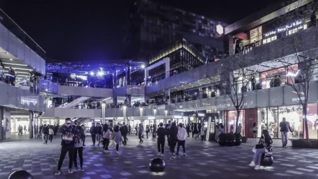 'S nachts, lopen onder de jonge mensen van de mode in het Sanlitun Village winkelen vierkant, Beijing, China