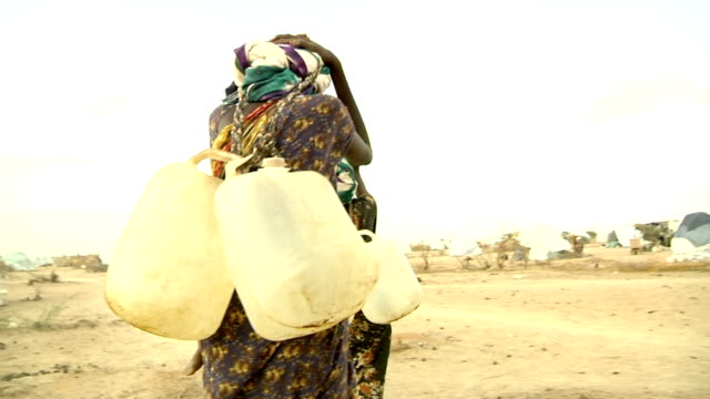 at refugee camp Women carrying water gallons with their heads on July 30 2011 in Dadaab Kenya